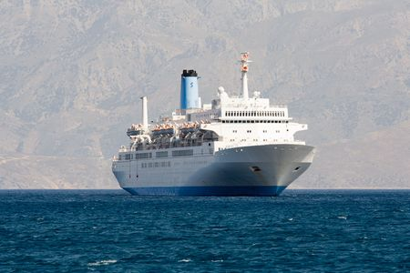 Tourist white cruise sea liner is sailing in rocky bay on the mountain background