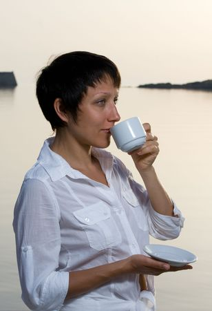 Young dressed white brunette woman meets sunrise drinking morning coffee Stock Photo - 7361532