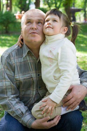 tenderly: Bambina teneramente abbraccia il nonno e si siede sulle braccia nel parco. Entrambi cercare  Archivio Fotografico