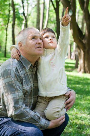 tenderly: Bambina teneramente abbraccia nonno nel parco, si siede sulle braccia e punti. Entrambi cercare  Archivio Fotografico
