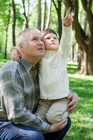 Little girl tenderly embraces grandfather in the park, sits on his arms and points up. Both look up photo
