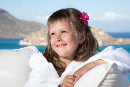 Portrait of happy smiling little girl with flowered hair in white bathrobe relaxing on terrace divan on the sea background photo