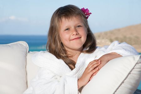 Portrait of happy smiling little girl with flowered hair in white bathrobe relaxing on terrace divan and looking at camera on the sea background photo
