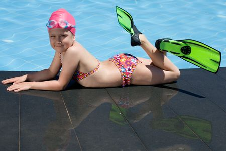flippers: Smiling cute little child in bathing cap, glasses and fins is lying on the swimming pool ledge