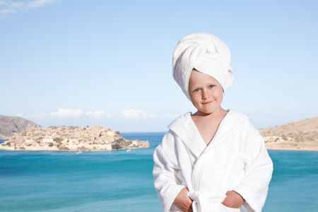 Portrait of happy smiling little girl with towel on the head in white bathrobe relaxing on terrace and looking at camera on the sea background photo