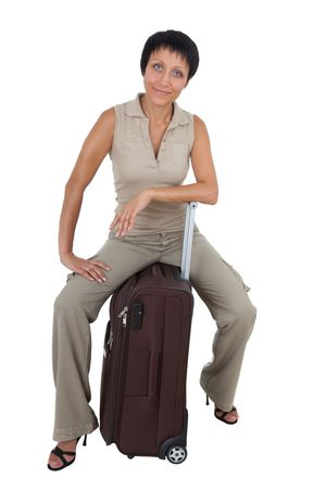 Smiling young tourist haircut woman dressed buff trouser suit sits on the  brown traveling suitcase isolated photo