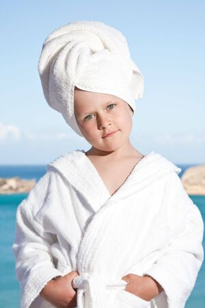 Portrait of happy smiling little girl with towel on the head in white bathrobe relaxing on terrace on the sea background photo