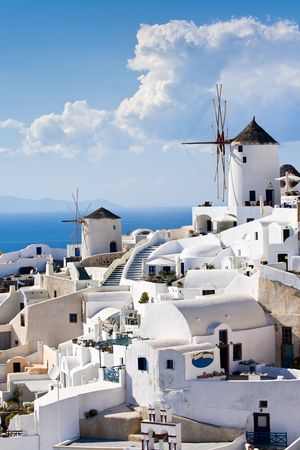 labyrinthine: Old-style white traditional windmills in terraced village Oia of Cyclades island Santorini Greece on the blue Aegean Sea and sky background