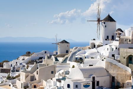 cyclades: Old-style white traditional windmills in terraced village Oia of Cyclades island Santorini Greece on the blue Aegean Sea and sky background