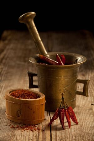 Bunch of red hot cayenne pods, bronze pounder and milled chilli pepper in wooden bowl on wooden table and black background photo