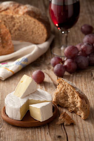 Piece and wheel of traditional Normandy soft cheese Camembert with country homemade bread, grapes and glass of red wine on wooden table Stock Photo