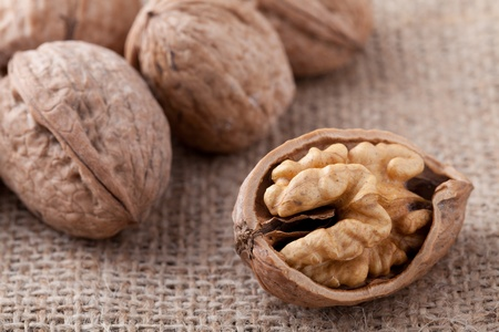 circassian: Core of cracked nut close-up, group of brown Circassian walnuts on the sackcloth background