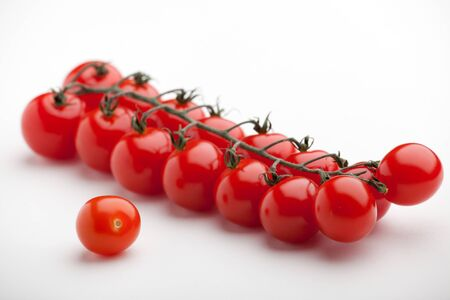 Cluster of fresh ripe red cherry tomatoes close-up on white background photo