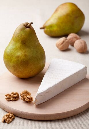 circassian: Ripe green pears, piece of white soft cheese brie, cores of Circassian walnuts on wooden board and linen tablecloth Stock Photo