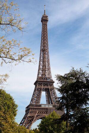 national landmark: Punto di riferimento nazionale europeo Torre Eiffel attraverso foglie degli alberi del parco in primavera nella citt� di Parigi Francia sullo sfondo del cielo blu