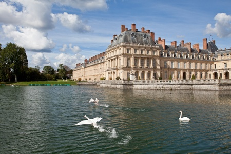 Medieval landmark royal hunting castle Fontainbleau near Paris in France and lake with white swans Stock Photo