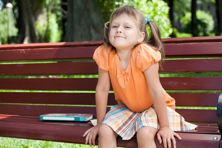Little cute smiling girl preschooler with open book who is sitting on the wooden bench in summer park photo