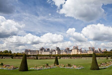 Medieval landmark royal hunting castle Fontainbleau near Paris in France and garden with flowers on the cloudy blue sky background Stock Photo