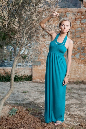 Portrait of romantic gentle elegant young blond woman with blue eyes and dress, near olive tree on the Mediterranean style court and stone wall background photo