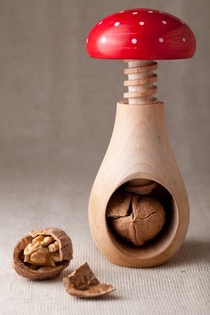 circassian: Cracked brown Circassian walnuts, nut core, shell, wooden handmade nutcracker like fungus amanita on linen tablecloth background