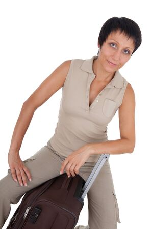 buff: Smiling young tourist haircut woman dressed buff trouser suit sits on the  brown traveling suitcase isolated Stock Photo