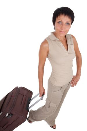 Smiling young tourist haircut woman dressed buff trouser suit stands with brown traveling suitcase isolated photo