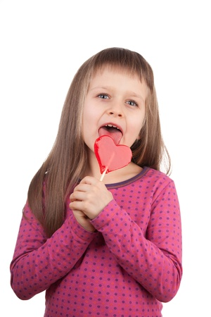 Portrait of little cute happy girl 7-8 years old licking red sweet lollipop in the shape of heart isolated photo