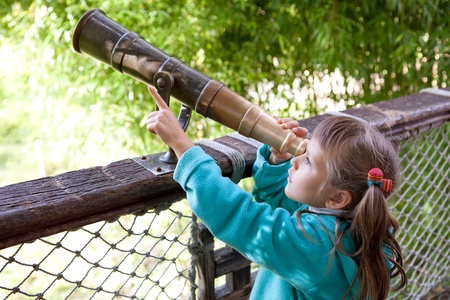 Little inquisitive girl preschooler discovers surroundings on observation balcony in spring park through old-style telescope and point a finger at finding Stock Photo