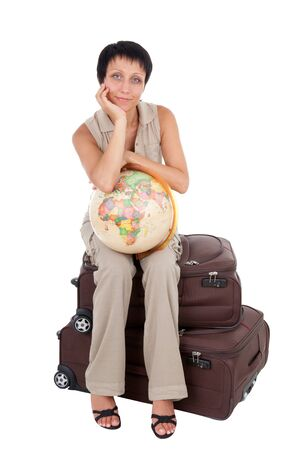 Smiling young tourist haircut woman dressed buff trouser suit sits on the  brown traveling suitcase with globe isolated photo
