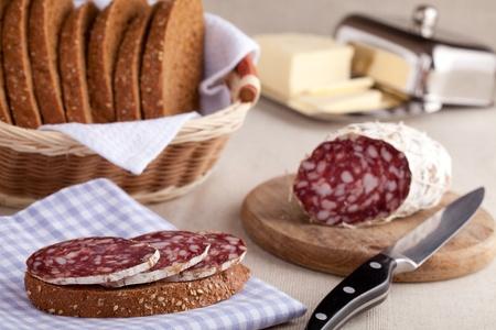 Served kitchen table, sandwich on napkin, salami, breadbasket, sliced bread photo