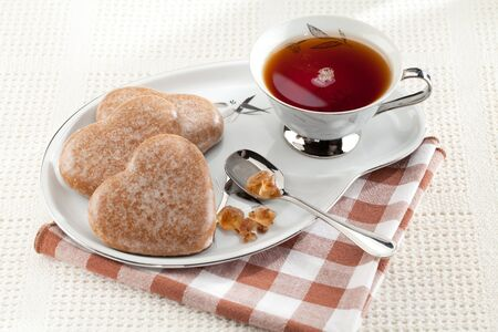 tea and biscuits: Served cookies heart shape, crystal brown sugar in silver spoon, black tea in cup on saucer on plaid textile tablecloth