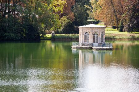 Wonderful Renascence style pavilion on calm pond with trees reflection in many-colored autumn garden photo