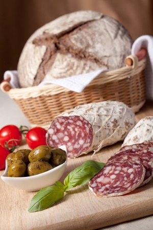 Traditional sliced salami on wooden board, fresh cherry tomatoes, green olives in salad bowl, brown bread loaf in wicker breadbasket photo