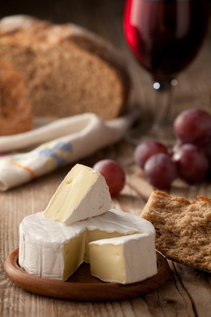 Piece and wheel of traditional Normandy soft cheese Camembert with country homemade bread, grapes and glass of red wine on wooden table photo