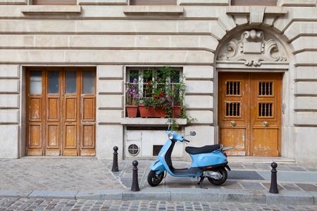 parked: Blue retro motor fiets geparkeerd tussen twee houten deuren op stoep in de buurt van oude stijl huis en geplaveide straat in Europese stad Redactioneel