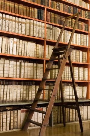 biblioteca: Estantes con libros antiguos en la biblioteca y la tijera de madera