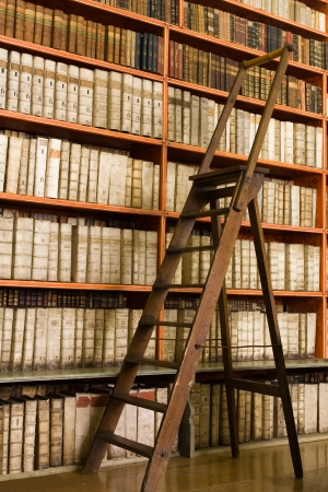 archives: Shelves with old books in the library and wooden stepladder
