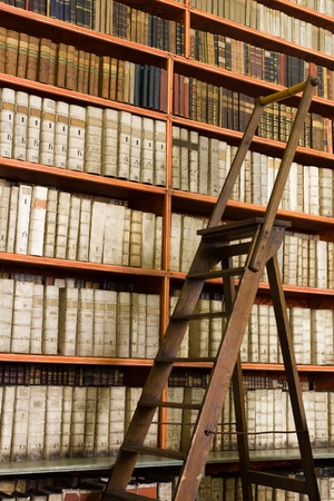Shelves with old books in the library and wooden stepladder Stock Photo - 10004765