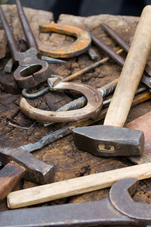 farriery: Rusty blacksmith tools and horseshoes on wooden log