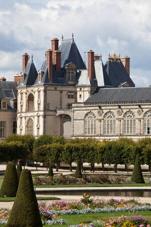 Medieval landmark royal hunting castle Fontainbleau near Paris in France and garden with flowers on the cloudy blue sky background Editorial