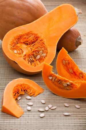 woven surface: Madura calabazas de color naranja y la otra mitad en rodajas segmentos carnosos y semillas blancas en paja tejida rural superficie y el fondo de rayas
