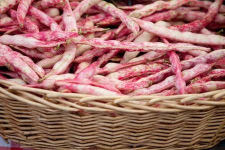 Fresh pods of vegetable speckled red string beans macro in woven basket close-up at the table Stock Photo