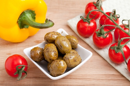 fascicle: Bunch of ripe red cherry tomatoes  on white napkin, green olives in white glass salad bowl close-up and yellow paprika on wooden table
