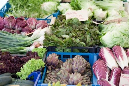 Variety of fresh vegetarian greens, lettuce, cabbage in plastic transport bag at open farmer's street vegetable market photo