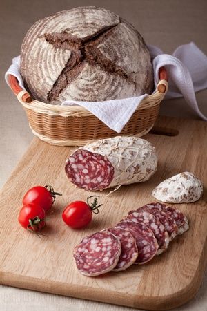 Traditional sliced salami on wooden board, fresh cherry tomatoes brown bread loaf in wicker breadbasket photo