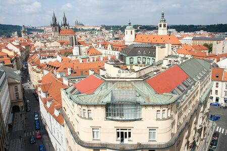 mansard: Top view cityscape on facades, red tiled mansard roofs, old Prague streets and district, Gothic cathedrals on blue sky background