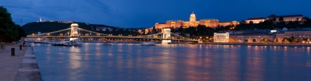 chain bridge: Panoramic night cityscape on landmark Gellert and castle hill Buda, baroque royal palace, Szechenyi chain bridge over Danube river in twilight Budapest Hungary