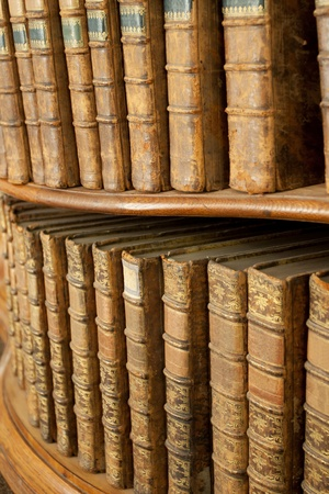 Hard covers of rust old medieval literary books on wooden shelves in bookcase Stock Photo