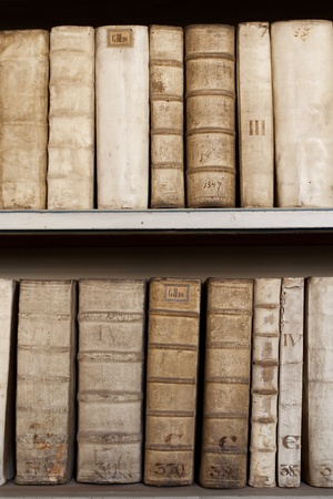 Hard covers of rust moldy ancient books monuscripts on wooden shelves in bookcase Stock Photo
