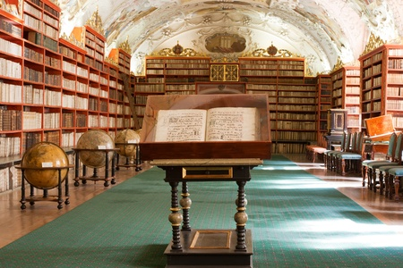 OLD LIBRARY: Library with ancient books, old globes, bookshelves, furniture in Theological Hall with stucco decoration Strahov monastery Czech Republic Prague